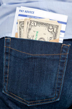 recompense: Photo of a payslip and cash sticking out of the back pocket in a pair of jeans  Stock Photo