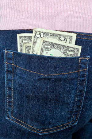 cashflow: Photo of some US banknotes in the back pocket of a womans jeans