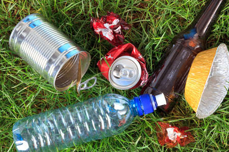 Photo of litter on grass, bottles, cans and wrappers.