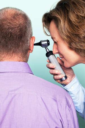 dolor de oido: Foto de una mujer médico examinar el oído pacientes utilizando un otoscopio