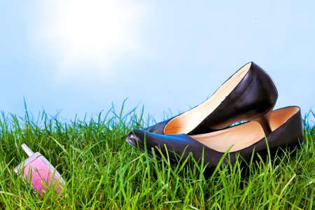 womens day: Photo of womens high heel shoes and a mobile phone on grass against a bright blue sky with sunshine  Stock Photo