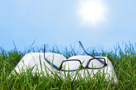 Photo of an open book and spectacles outdoors in grass on a bright sunny day photo