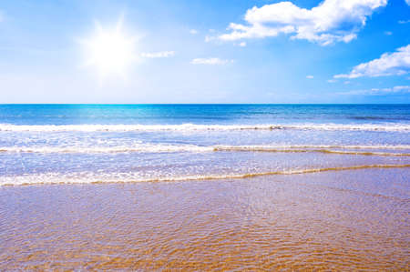 Photo of waves crashing on a golden beach with the sun shining in a blue sky