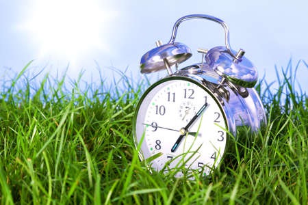 Photo of a chrome alarm clock outdoors sitting in grass on the morning of a bright sunny day.