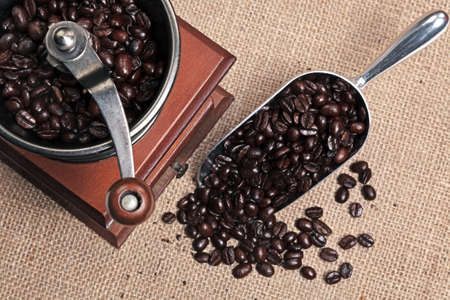 Photo of a hand operated traditional coffee grinder with a scoop full of arabica beans on a hessian background. Stock Photo - 13248064