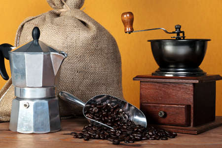 Still life photo of a  caffettiera or moka pot with traditional coffee grinder hessian sack and arabica beans in a scoop. photo