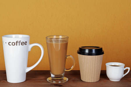 Photo of four types of coffee including a latte, espresso, mocha and cappuccino in different styles of cups, mugs and containers. Stock Photo