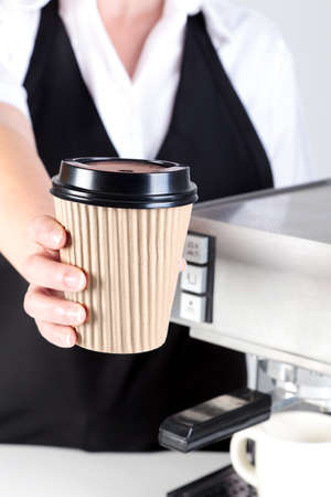 Photo of a Barista handing you a coffee in a disposable paper takeaway cup. photo