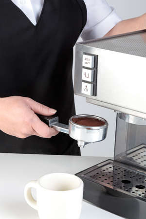 Photo of a barista putting a porta-filter full of freshly ground coffee into an espresso machine. Stock Photo - 13263412