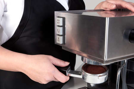 baristas: Photo of a barista putting a porta-filter full of freshly ground coffee into an espresso machine.