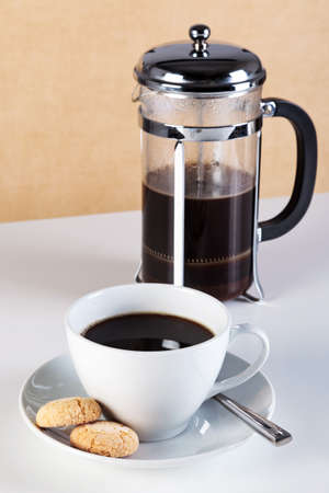 Photo of a cup of coffee with Amaretti biscuits on the saucer and a cafetiere full of freshly brewed coffee. Stock Photo - 13263410