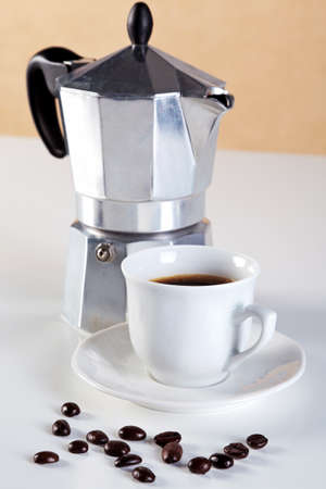 Photo of an Italian Caffettiera or Moka pot with a cup of freshly brewed espresso coffee, a few arabica beans in front. These are also referred to as a Stove pot and are made from aluminium. Stock Photo - 13263406