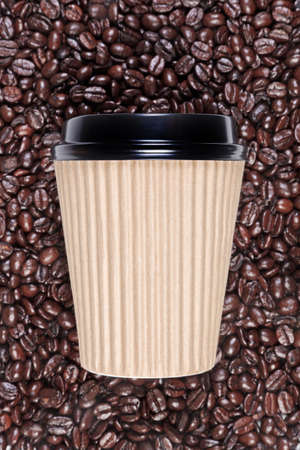 Photo of a disposable paper coffee cup with a mixture of arabica and robusta beans in the background. photo