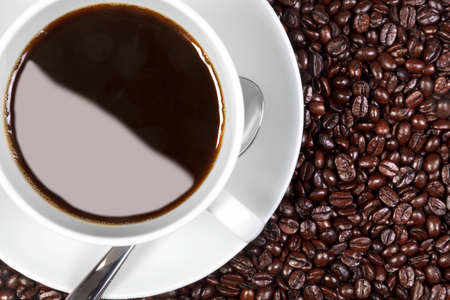 Overhead photo of a cup of coffee sitting on fresh roasted arabica and robusta coffee beans. Stock Photo - 13263415