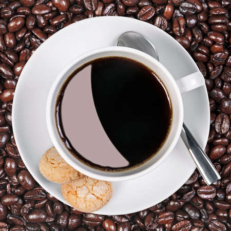 robusta: Overhead photo of a coffee cup with amaretti biscuits on the side with a background of fresh roasted arabica and robusta coffee beans.