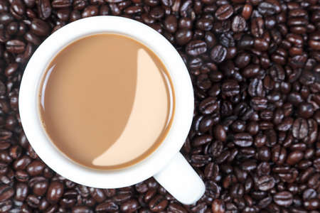 Overhead photo of a mug full of hot coffee on a mixture of arabica and robusta coffee beans. Stock Photo - 13312659