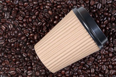 Photo of a takeaway disposable paper coffee cup on a background of fresh roasted arabica and robusta beans. photo