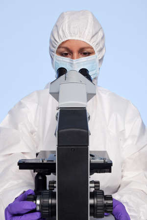 biochemist: Photo of a biochemist looking at a laboratory microscope.
