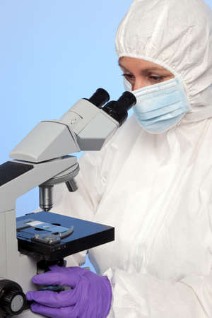specimen testing: Photo of a biochemist looking through a stereo optical laboratory microscope at a specimen on a slide.