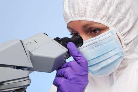 overol: Foto de un bioqu�mico mirando a trav�s de un microscopio de laboratorio est�reo �ptica a una muestra en un portaobjetos.