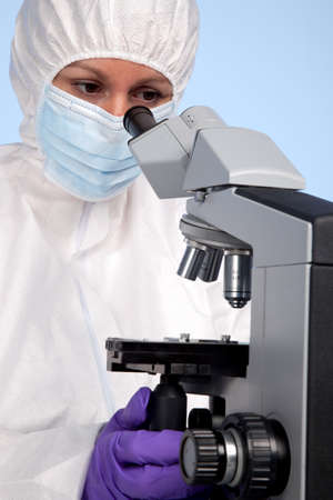 Photo of a biochemist looking through a stereo optical laboratory microscope at a specimen on a slide. photo