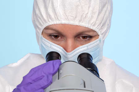 biochemist: Photo of a biochemist looking through the eyepieces of a stereo optical laboratory microscope. Stock Photo