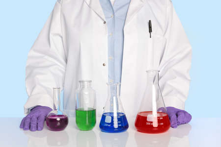 Photo of a chemistry teacher or scientist standing at a desk/counter with a row of chemicals in glass flasks and beakers in front of her. Stock Photo - 13508335
