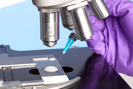 ivf: Photo of a sperm sample on a microscope slide with a syringe being used to extract an embryology specimen for analysis.