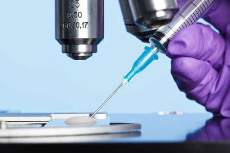 Foto van een sperma monster op een microscoopglaasje met een injectiespuit worden gebruikt om een embryologie monster voor analyse extraheren. Stockfoto