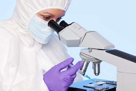 coverall: Photo of an embyologist examining a sperm sample through a stereo laboratory microscope and using a sysringe to extract a specimen for analysis. Stock Photo