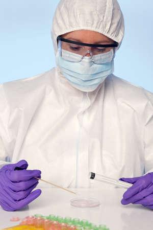 specimen testing: Foto de un t�cnico de laboratorio que tome una muestra de una placa de Petri.