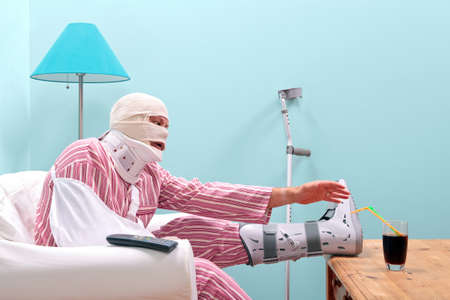 Photo of a injured man in pyjamas with a bandaged head, leg cast, arm sling and neck brace struggling to reach a drink on the table in front of him.