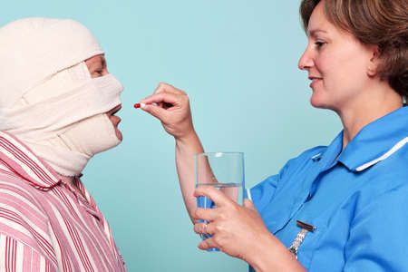 incapacitated: Photo of a nurse giving a patient some medicine in the form of a pill.