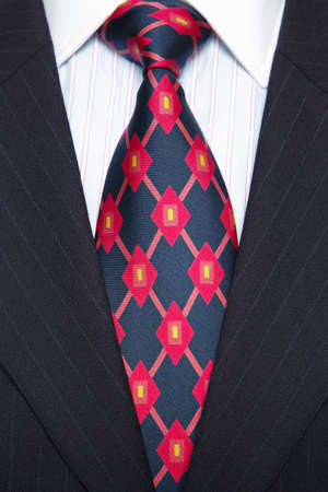 Photo of a blue pinstripe suit with blue striped shirt and red and blue patterned tie photo