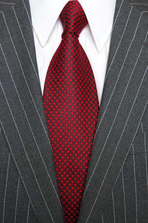Foto de un traje gris a rayas con camisa blanca llana y una corbata roja con dibujos