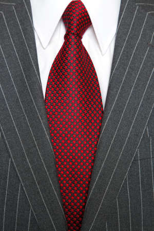 Photo of a grey pinstripe suit with plain white shirt and red patterned tie photo