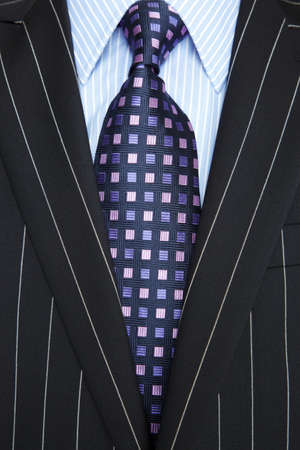 in men's shirt: Photo of a black pinstripe suit with blue striped shirt and purple and blue patterned tie