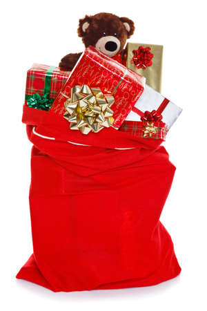 Red Christmas sack full of gift wrapped presents, isolated on a white background