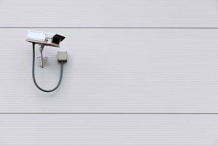 Photo of a CCTV security camera on the wall of a building photo