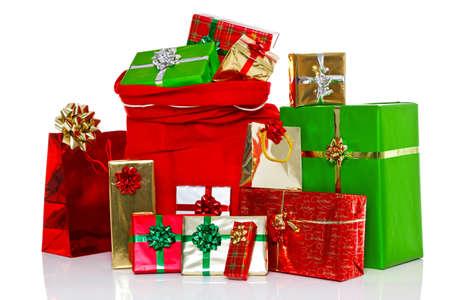Een rode kerst zak vol en wordt omringd door gift verpakte cadeautjes, geïsoleerd op een witte achtergrond.