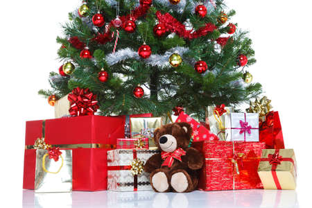 Decorated Christmas tree with baubles and tinsel surrounded by gift wrapped presents and a teddy bear, isolated on a white background. The teddy is generic, not a brand name bear and does not breach any trademark or copyright.