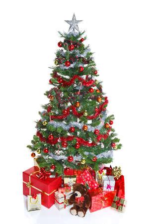 Decoración del árbol de Navidad con bolas y oropel rodeadas de regalos envueltos para regalo y un oso de peluche, aislado en un fondo blanco. El peluche es genérico, no un oso de marca y no infringe ninguna marca registrada o derechos de autor. Foto de archivo