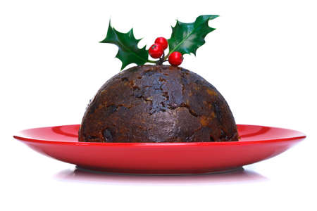 A steamed Christmas pudding with holly on top isolated on a white background.