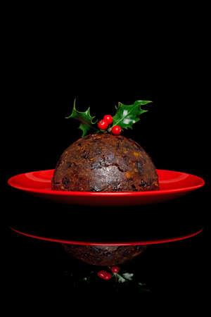 plum pudding: Foto di un budino di Natale con agrifoglio e bacche in alto, su sfondo nero.