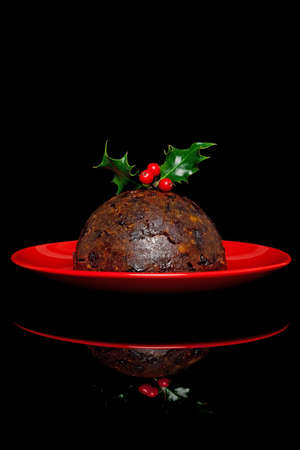 Photo of a traditional Christmas pudding with holly and berries on top, on a black background.