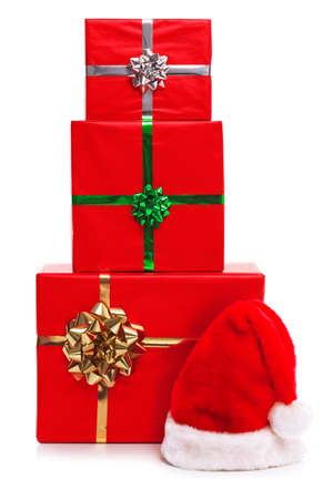 Santa Claus hat and three red gift wrapped Christmas presents with ribbons and bows, isolated on a white background. Stock Photo - 15860544