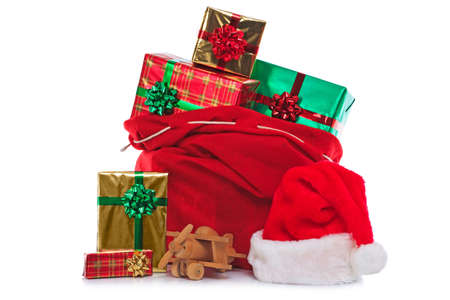 Photo of a red Santa Claus hat and sack full of gift wrapped presents and toys, isolated on a white background. photo