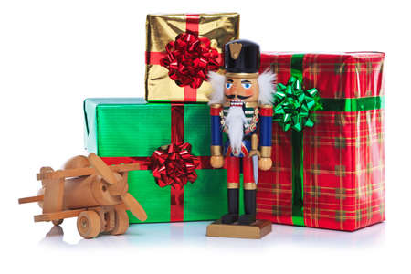 Photo of a Christmas toy wooden soldier with wooden plane and other gift wrapped presents, isolated on a white background. Stock Photo - 15860551