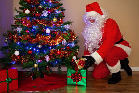 Santas Claus delivering presents and putting the gifts under the Christmas tree. His other names from around the world include Father Christmas, P&Atilde,&uml,re No&Atilde,&laquo,l, Pap&Atilde,&iexcl, Noel, Babbo Natale, Sinterklaas, Christkind and Weihn Stock Photo - 15860552