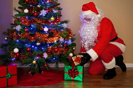 sinterklaas: Santas Claus Geschenke auszuliefern und setzen die Geschenke unter dem Weihnachtsbaum. Seine anderen Namen aus der ganzen Welt geh�ren Weihnachtsmann, P� �, re No�l �, l, Papa, �, Noel, Babbo Natale, Sinterklaas, Christkind und Weihn Lizenzfreie Bilder